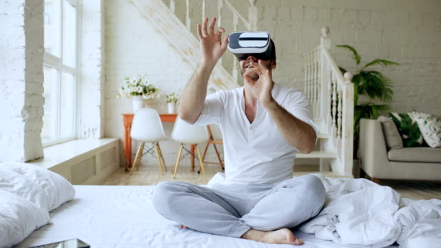 Young-cheerful-man-wearing-virtual-reality-headset-watching-360-VR-video-movie-sitting-in-the-bed-at-home