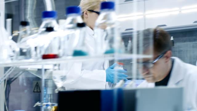 Seguimiento-de-tiro-de-joven-mujer-científico-caminando-con-caso-de-tubos-de-ensayo-a-través-de-laboratorio-ocupado-Masculino-y-femenino-científicos-de-diferente-edad-que-trabajan-en-este-laboratorio-de-vanguardia-