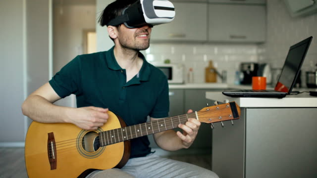 Happy-young-man-sitting-at-kitchen-learning-to-play-guitar-using-VR-360-headset-and-feels-him-guitarist-at-concert-at-home