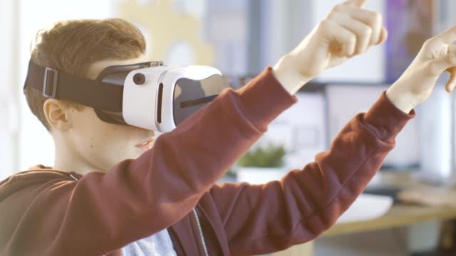 En-un-muchacho-de-clase-de-ciencia-de-computadora-uso-de-casco-de-realidad-Virtual-trabaja-en-un-proyecto-de-programación-