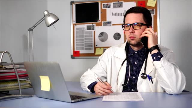 Médico-varón-en-la-clínica-sentado-en-la-mesa-y-hablando-por-teléfono-inteligente-