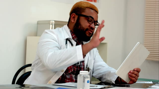 African-american-male-doctor-explaining-xray-results-to-patient-via-video-call-on-tablet