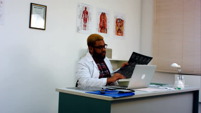 Male-doctor-discussing-brain-xray-image-with-patient-on-skype