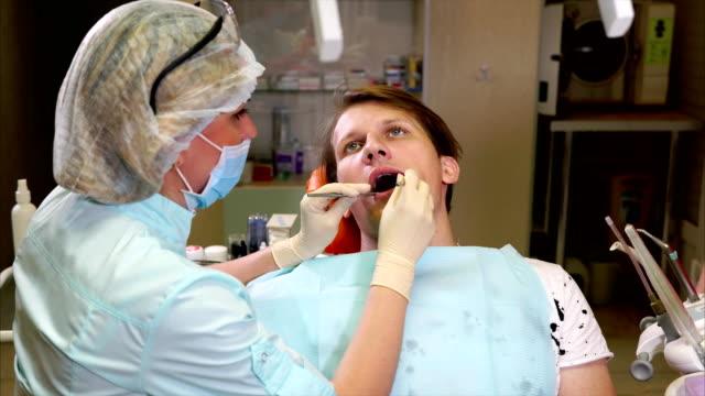 Médico-dentista-realiza-un-examen-de-primario-de-la-cavidad-bucal-del-paciente