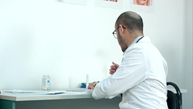 Doctor-masculino-sacudida-por-termómetro-y-entregárselo-a-la-paciente
