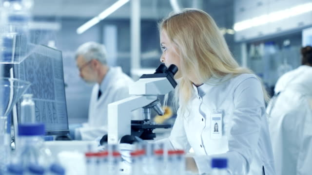 Female-Research-Scientist-Looks-at-Biological-Samples-Under-Microscope-Types-Results-into-Computer-She-and-Her-Colleagues-Work-in-a-Big-Modern-Laboratory/-Medical-Centre-
