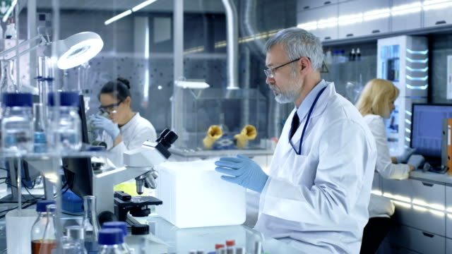 Senior-Medical-Research-Scientist-Opens-Refrigerator-Box-Takes-Out-Petri-Dish-with-Samples-and-Examines-it-He-Works-in-a-Busy-Modern-Laboratory-Center-