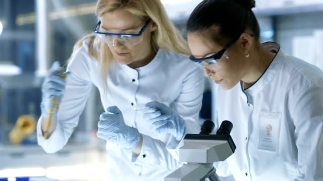Medical-Research-Scientist-Drops-Sample-on-Slide-and-Her-Colleague-Examines-it-Under-Microscope-They-Work-in-a-Modern-Laboratory-