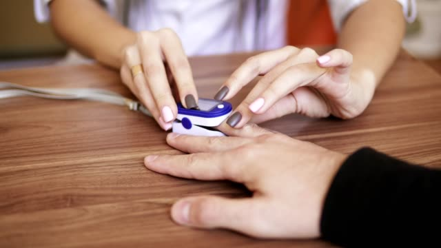 Pulse-oximeter-placed-on-an-unrecognizable-man-s-finger-is-examining-his-heart-rate-and-pulse-during-medical-check-up-Shot-in-4k