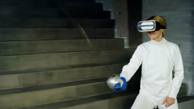 Konzentrierte-Fechter-Frau-mit-virtual-Reality-Kopfhörer-für-Fechten-Training-Simulator-Spiel-drinnen-spielen