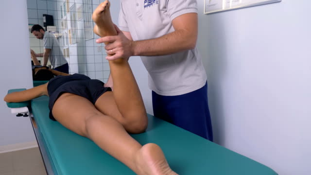 Physiotherapy-session:-Physiotherapy-massages-a-patient-s-leg