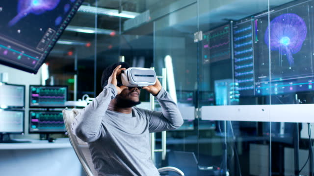 In-Laboratory-Scientist-Wearing-Virtual-Reality-Headset-Sitting-in-a-Chair-Interacts-With-Monitors-Showing-Brain-Activity-Information-Modern-Brain-Study/-Neurological-Research-Center-