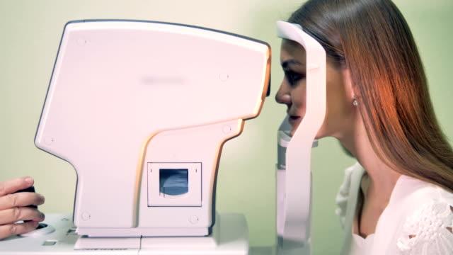 Vista-de-lado-de-una-señora-joven-de-poner-su-cabeza-en-una-máquina-médica-y-recibiendo-sus-ojos-comprobar