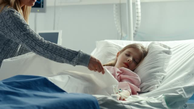 Cute-Little-Girl-Sleeps-on-a-Bed-in-the-Children-s-Hospital-Caring-Mother-Covers-Her-with-a-Blanket-and-Caresses-Her-Forehead-Modern-Pediatric-Ward-