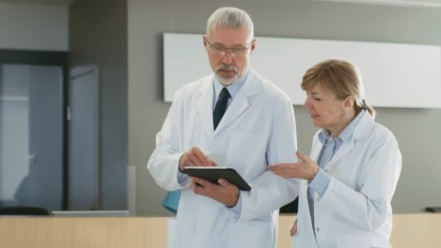 En-el-Hospital-los-médicos-caminando-por-el-Lobby-tener-discusión-mientras-uso-de-Tablet-PC-En-el-fondo-los-pacientes-y-personal-médico-Nuevo-centro-médico-totalmente-funcional-moderna-