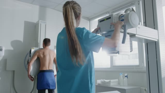In-the-Hospital-Man-Standing-Face-Against-the-Wall-While-Medical-Technician-Adjusts-X-Ray-Machine-For-Scanning-Scanning-for-Fractures-Broken-Limbs-Chest-Cancer-or-Tumor-Modern-Hospital-with-Technologically-Advanced-Medical-Equipment-