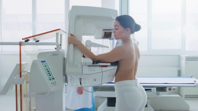 En-el-Hospital-lado-vista-tiro-de-Topless-mujer-paciente-someterse-a-mamografías-procedimiento-Mujer-joven-saludable-hace-exploración-mamografía-preventiva-del-cáncer-Moderno-Hospital-con-máquinas-de-alta-tecnología-