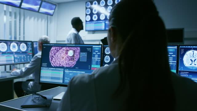 Sobre-el-tiro-de-hombro-de-mujer-científico-médico-trabajando-con-exploración-del-cerebro-imágenes-en-un-ordenador-Personal-en-laboratorio-Centro-de-investigación-neurológica-trabajando-en-curar-tumores-cerebrales-