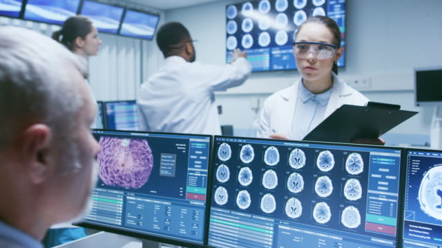 Senior-Medical-Scientist-Consults-Female-Apprentice-with-Clipboard-He-Works-with-CT-Brain-Scan-Images-on-a-Personal-Computer-in-Laboratory-Neurologists-in-Research-Center-Work-on-Brain-Tumor-Cure-