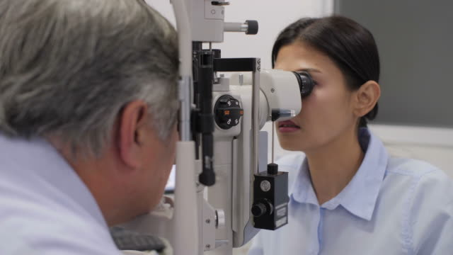 Doctor-checking-senior-patients-eyes