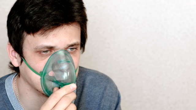 Use-nebulizer-and-inhaler-for-the-treatment-Young-man-inhaling-through-inhaler-mask-Side-view-