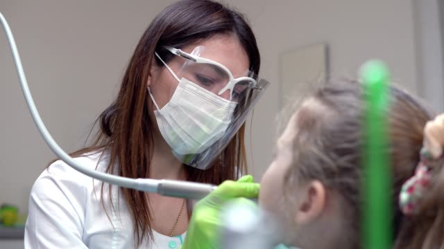 Dentist-cleans-girl-s-teeth-with-professional-toothpaste-Girl-with-white-teeth-at-the-dentist-s-office-Shot-in-4k