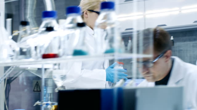Follow-up-Shot-of-Young-Female-Scientist-Walking-with-Case-of-Test-Tubes-Through-Busy-Laboratory-Male-and-Female-Scientists-of-Different-Age-Working-in-this-State-of-the-Art-Laboratory-