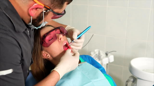 Doctor-orthodontist-with-glasses-whitens-the-teeth-of-a-young-woman-with-a-laser