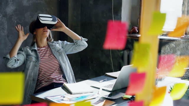 Attractive-young-woman-is-sitting-at-table-and-wearing-virtual-reality-glasses-She-is-moving-hands-and-and-having-VR-experience-in-modern-lof-office