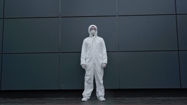 científico-asiático-en-traje-de-protección-de-pie-cerca-de-la-construcción
