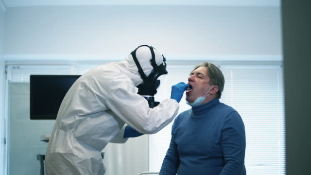 A-clinic-worker-takes-man-s-smear-for-coronavirus-test-during-coronavirus-pandemic-Coronavirus-covid-19-Infected-Patient-during-test-in-hospital-