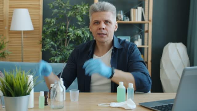 Portrait-of-adult-man-making-hand-sanitizer-at-home-holding-bottles-looking-at-camera-talking