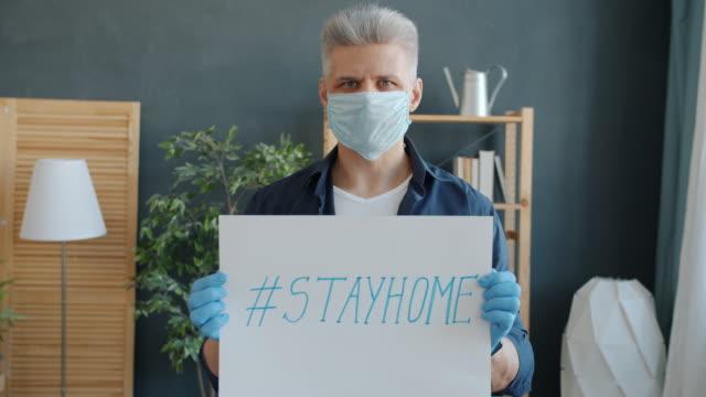 Retrato-a-cámara-lenta-del-hombre-adulto-que-lleva-máscara-y-guantes-sosteniendo-el-cartel-del-stayhome-en-casa