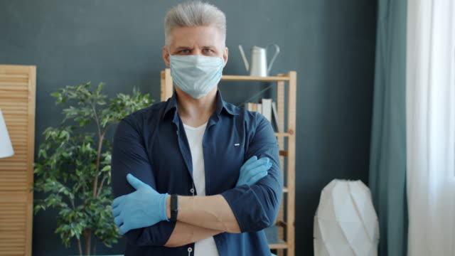 Retrato-de-hombre-adulto-con-máscara-médica-preventiva-y-guantes-de-pie-en-el-apartamento-con-los-brazos-cruzados