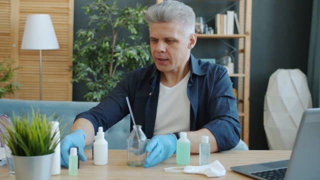 Portrait-of-handsome-guy-making-home-made-hand-sanitizer-in-apartment-talking-looking-at-camera