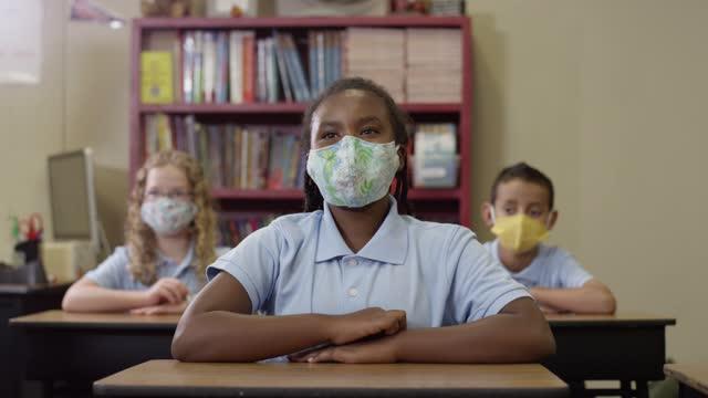 Los-niños-de-la-escuela-primaria-usan-máscaras-en-clase-mientras-la-niña-negra-levanta-la-mano