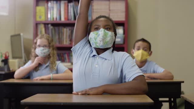 Junge-Schüler-tragen-Masken-und-hören-im-Unterricht-dann-schwarzeS-Mädchen-hebt-ihre-Hand