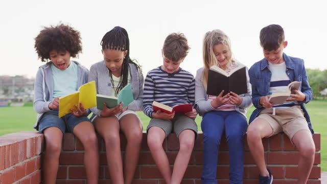 Grupo-de-niños-leyendo-libros-mientras-están-sentados-en-una-pared-de-ladrillos