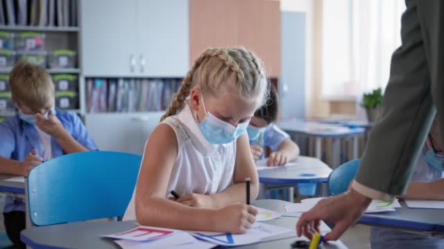 Schüler-in-medizinischen-Masken-die-Schularbeiten-am-Schreibtisch-im-Klassenzimmer-sitzen-Kinder-wieder-in-der-Schule-nach-covid-19-Quarantäne-und-Sperrung