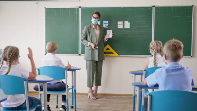 Studie-während-der-Pandemie-Lehrer-in-medizinischer-Maske-und-Brille-im-Unterricht-in-der-Nähe-von-Whiteboard-stellt-Schülern-Fragen-Schülerin-ist-bereit-zu-beantworten-und-hebt-die-Hand