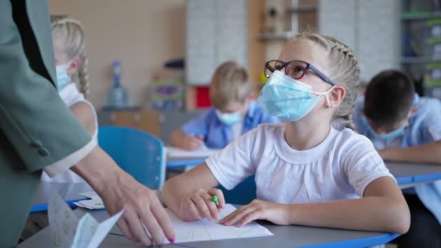 pupils-back-at-school-after-quarantine-and-lockdown-schoolgirl-in-glasses-and-medical-mask-doing-classwork-sitting-at-desk