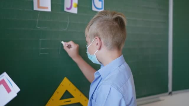 colegial-en-máscara-médica-en-la-pizarra-escribe-cartas-con-tiza-en-el-aula-en-la-escuela-después-de-la-cuarentena-y-el-encierro