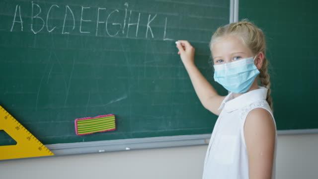 portait-de-colegiala-en-máscara-médica-escribe-en-tiza-el-alfabeto-Inglés-en-el-aula-la-mirada-del-alumno-en-la-cámara-cerca-de-la-pizarra-en-la-escuela
