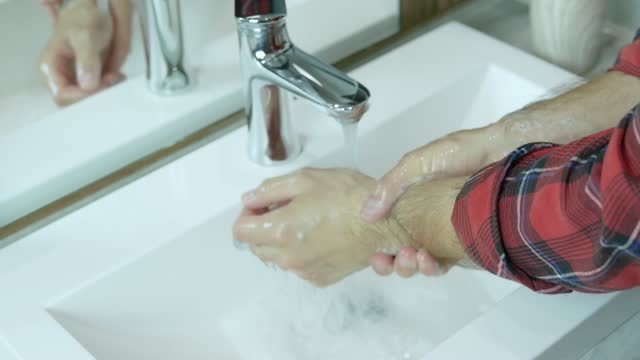 Wash-hands-with-soap-under-the-tap-with-water-close-up-male-hands-wash-bacteria-dirt-cleanliness-and-body-hygiene