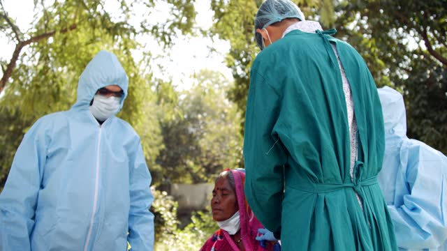 Medical-staff-doctors-outdoors-with-a-senior-female-in-rural-India