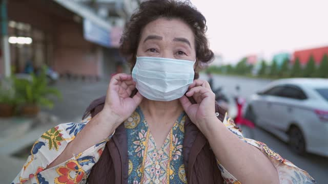 Asian-Senior-lady-wearing-protective-face-mask-standing-on-the-roadside-infectious-diseases-prevention-during-Corona-virus-covid-19-social-distancing-risk-of-illness-protection-waiting-for-vaccine