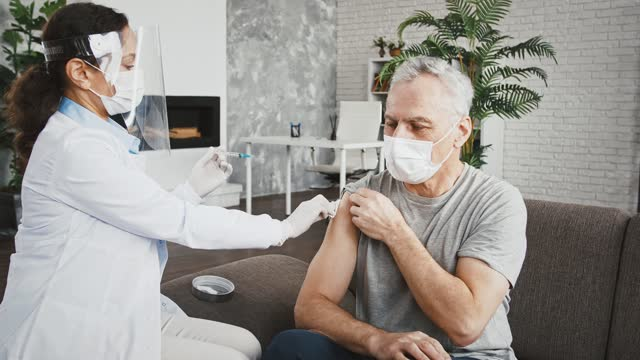 Woman-doctor-in-protective-mask-and-face-shield-is-injecting-vaccine-into-shoulder-of-aged-man-who-sitting-on-sofa-at-home