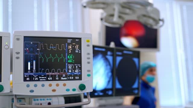 Sala-de-cuidados-intensivos-con-equipamiento-médico-moderno-Monitor-médico-de-la-UCI-que-muestra-la-condición-del-paciente-enfermo-La-pantalla-muestra-los-signos-vitales-del-paciente-Concepto-de-atención-médica-