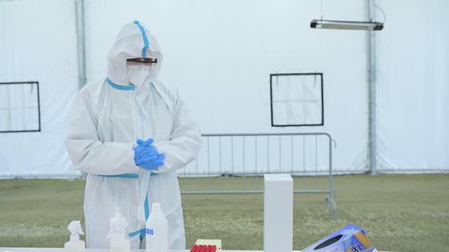 Hombre-en-traje-protector-con-máscara-que-sostiene-la-muestra-de-hisopo-después-de-una-prueba-de-conducción-para-covid-19-Prevención-y-control-de-infecciones-epidémicas-
