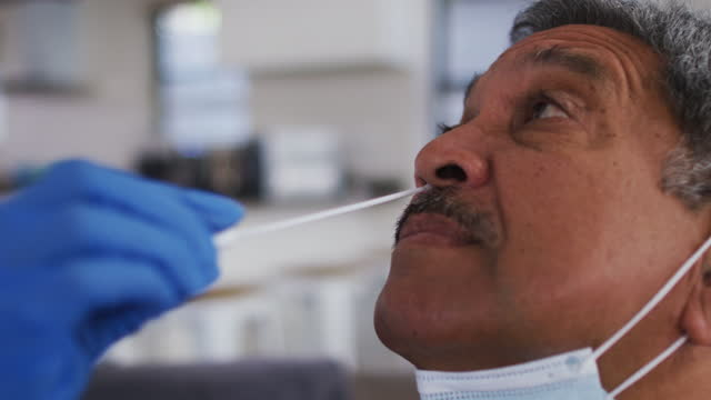 Mixed-race-female-doctor-wearing-mask-doing-swab-test-on-senior-man-at-home